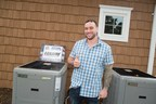 United States Marine Corps Corporal Kevin Vaughan stands in front of his new Luxaire Acclimate Ultra-High Efficiency cooling system that was donated by Johnson Controls through its distributor ABCO.
