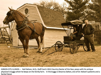 Gibson City, Illinois -- Neil Nelson, M.D. Staff Care's 2012 Country Doctor of the Year, poses with his antique physician's buggy, which he keeps on the family farm. In the buggy is Breanna Dalton, one of Dr. Nelson's patients and a family friend.  (PRNewsFoto/AMN Healthcare Services, Inc.)
