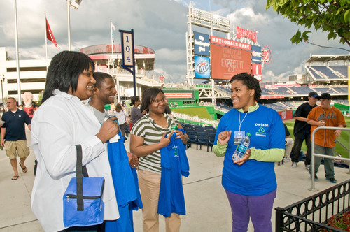 DASANI(R) Blue Crew member LaVette Spears rewarded Nationals fans, from left Queenetta LeFlore, Terrence Woods and Alecia Harrell, for partaking in everyday acts of greenness, like taking the Metro or recycling their beverage bottles. DASANI(R) celebrated Earth Month and its new eco-friendly PlantBottle(TM) packaging -- the first-ever fully recyclable plastic beverage bottle produced using plants -- by giving back to D.C. eco-Samaritans.  (PRNewsFoto/The Coca-Cola Company, Max Taylor)