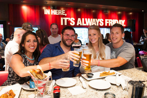 Guests share a toast while celebrating the grand reopening of the redesigned TGI Fridays(TM) in Braintree. ...