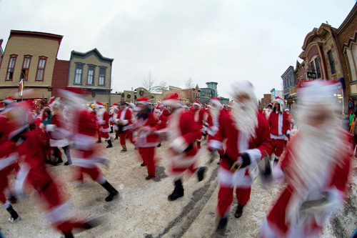 Participants in Race of the Santas in Breckenridge, Colo. sprint down Main Street as part of the annual fun run  ...