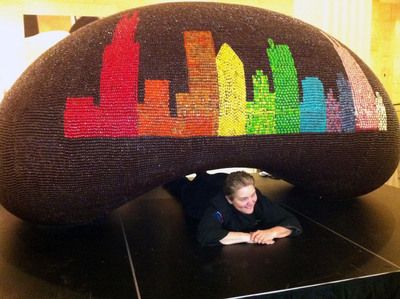 """Gloria Hafer, Culinary Arts Instructor for Chicago's After School Matters, poses under the giant chocolate """"bean"""" sculpture covered in Jelly Belly(R) jelly beans and Jelly Bean Chocolate Dips(R) now on display at Jelly Belly Visitor Center in Wisconsin. The candy creation is a replica of Chicago's """"Cloud Gate"""" by sculptor Anish Kapoor, which sits in Millennium Park. Photo credit: Jelly Belly Candy Company"""