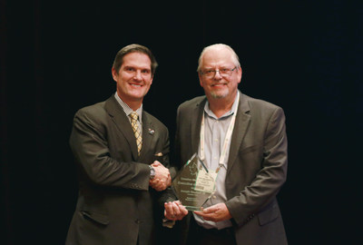 Covanta's Joey Neuhoff (left) receives the Canadian Waste Sector Executive of the Year award from OWMA CEO Robert Cook (right).
