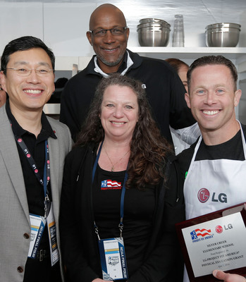 Trey Shearer of Silver Creek Elementary School accepts the award for winning the LG Coaches Cook-Off from William Cho, president and CEO of LG Electronics USA, left, basketball legend Clyde Drexler, back, and Project Fit America Executive Director Stacey Cook, front.  (PRNewsFoto/LG Electronics USA)