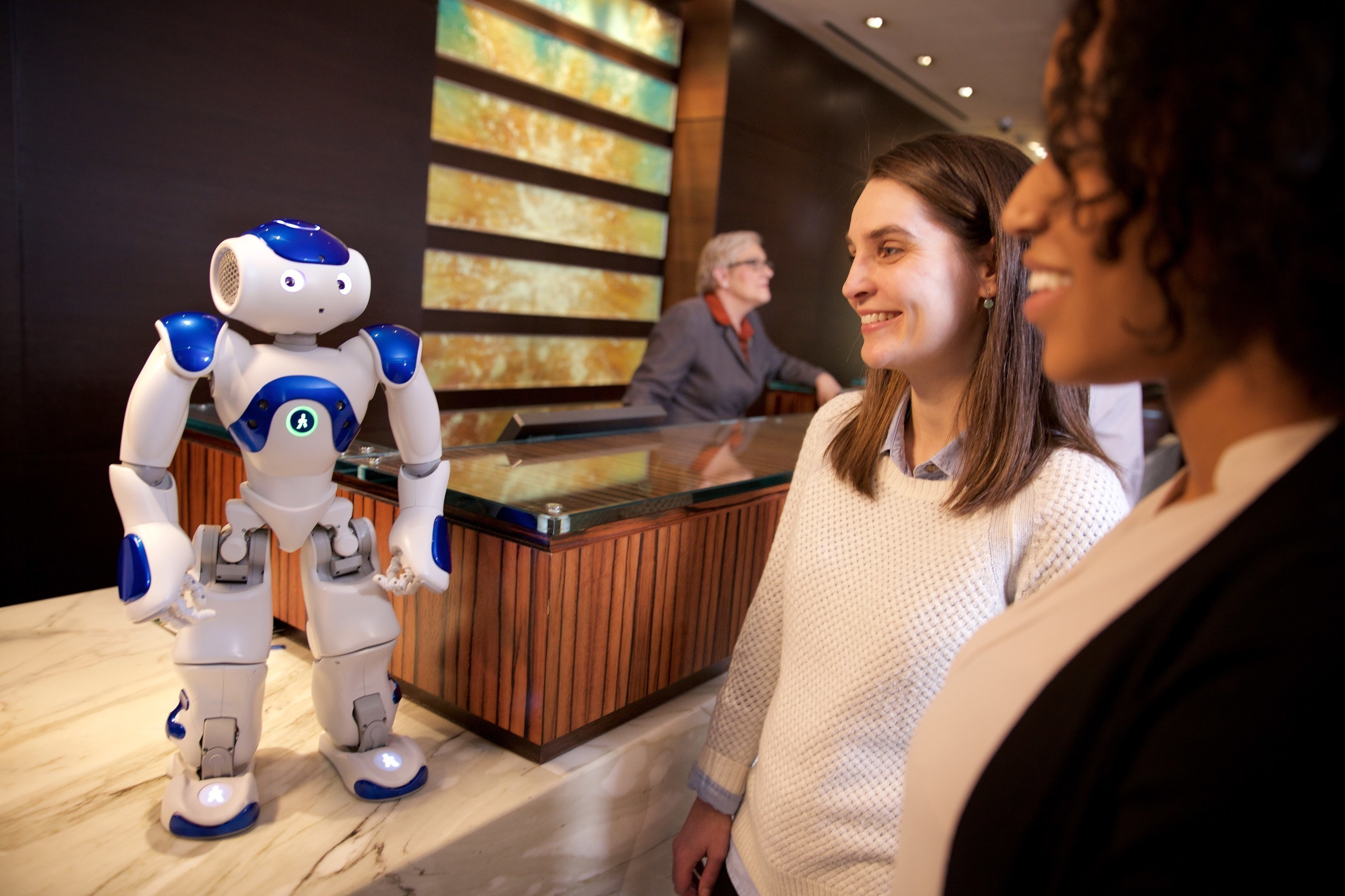 """Visitors to the Hilton Hotel in McLean, Va. meet """"Connie,"""" a robot concierge named after Conrad Hilton and powered by IBM Watson and WayBlazer. Connie, in pilot testing at the hotel, uses cognitive computing and machine learning to answer questions posed in natural language about the hotel, local tourist attractions and restaurants -- while learning with each interaction. (Photo courtesy of Green Buzz Agency/Feature Photo Service for IBM)"""