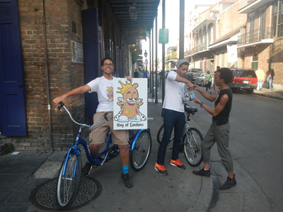The King of Condoms tricycle hits the streets of New Orleans, starting November 13, 2013.  Pictured L to R, King of Condoms Ambassadors Isaiah Jones, Sean Sylve, and a resident of NOLA getting condoms and free advice about safe sex and HIV testing.  (PRNewsFoto/ProofPilot)