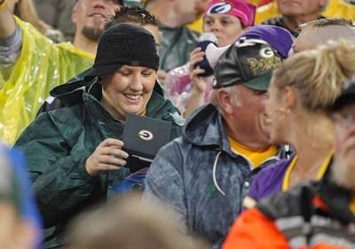 Happy fan discovers Aaron Rodgers Wallet under her Lambeau Field stadium seat (PRNewsFoto/Associated Banc-Corp)