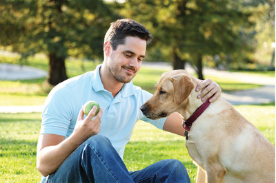 Man plays fetch with dog in the park.