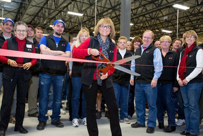 Kathie Leonard, president and CEO of AMI cuts the ribbon at the grand opening of the $1.4 million expansion at its Kitty Hawk manufacturing facility in Auburn, ME. Employees and guests were on hand to recognize the investment and celebrate the milestone. (PRNewsFoto/Auburn Manufacturing, Inc.) (PRNewsFoto/AUBURN MANUFACTURING, INC.)