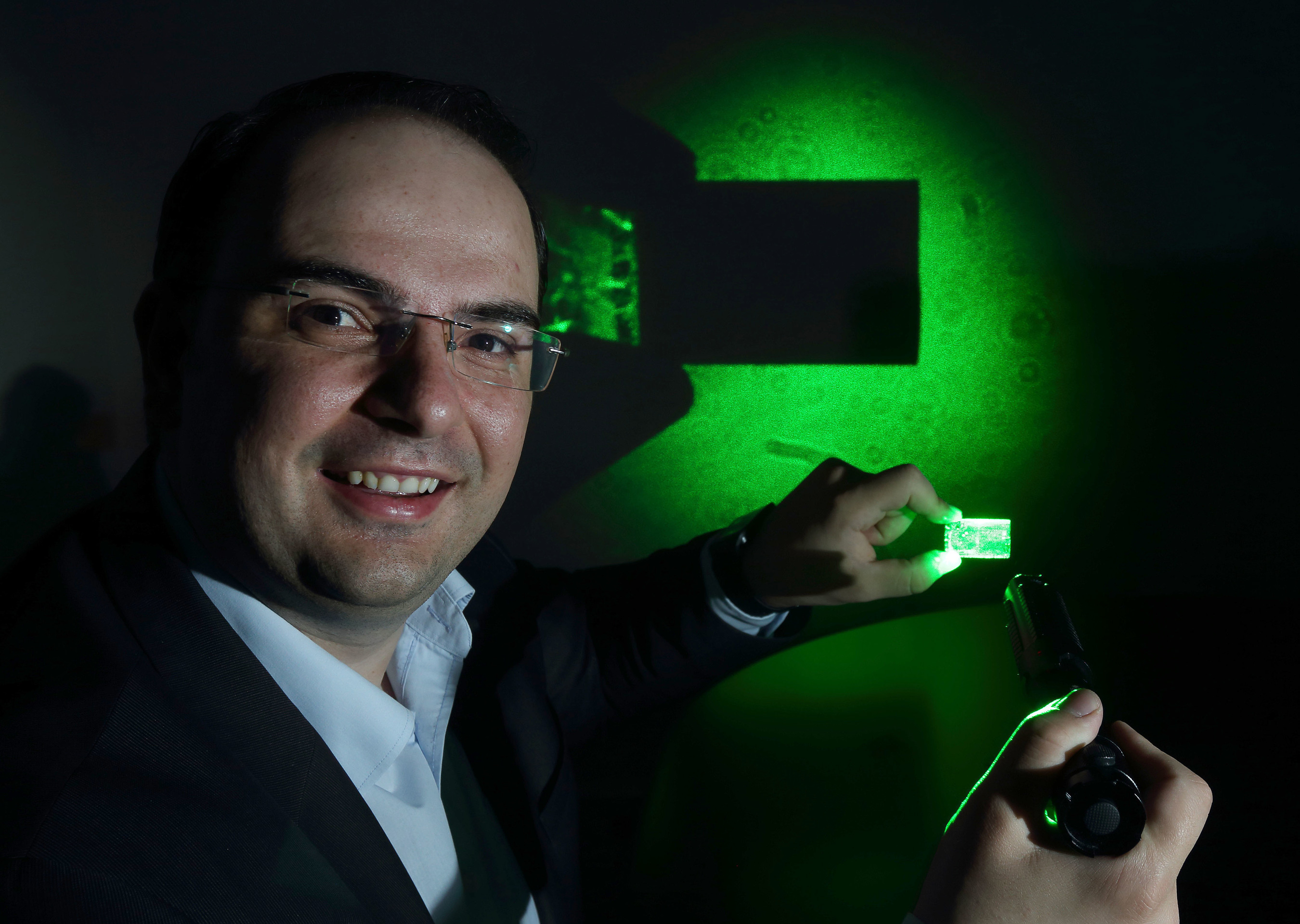 George Palikaras, President and CEO Lamda Guard demonstrates the effectiveness of his uniquely transparent yet 100% deflective nanocomposite windshield film at the announcement of the company's partnership with leading aircraft manufacturer Airbus. The film has the capacity to disable cockpit laser strikes. (PRNewsFoto/Lamda Guard)