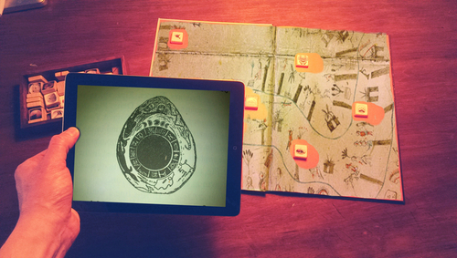 Using the iPad app to read the symbolic blocks placed on one of the maps in the book. (PRNewsFoto/Wuxia the Fox )