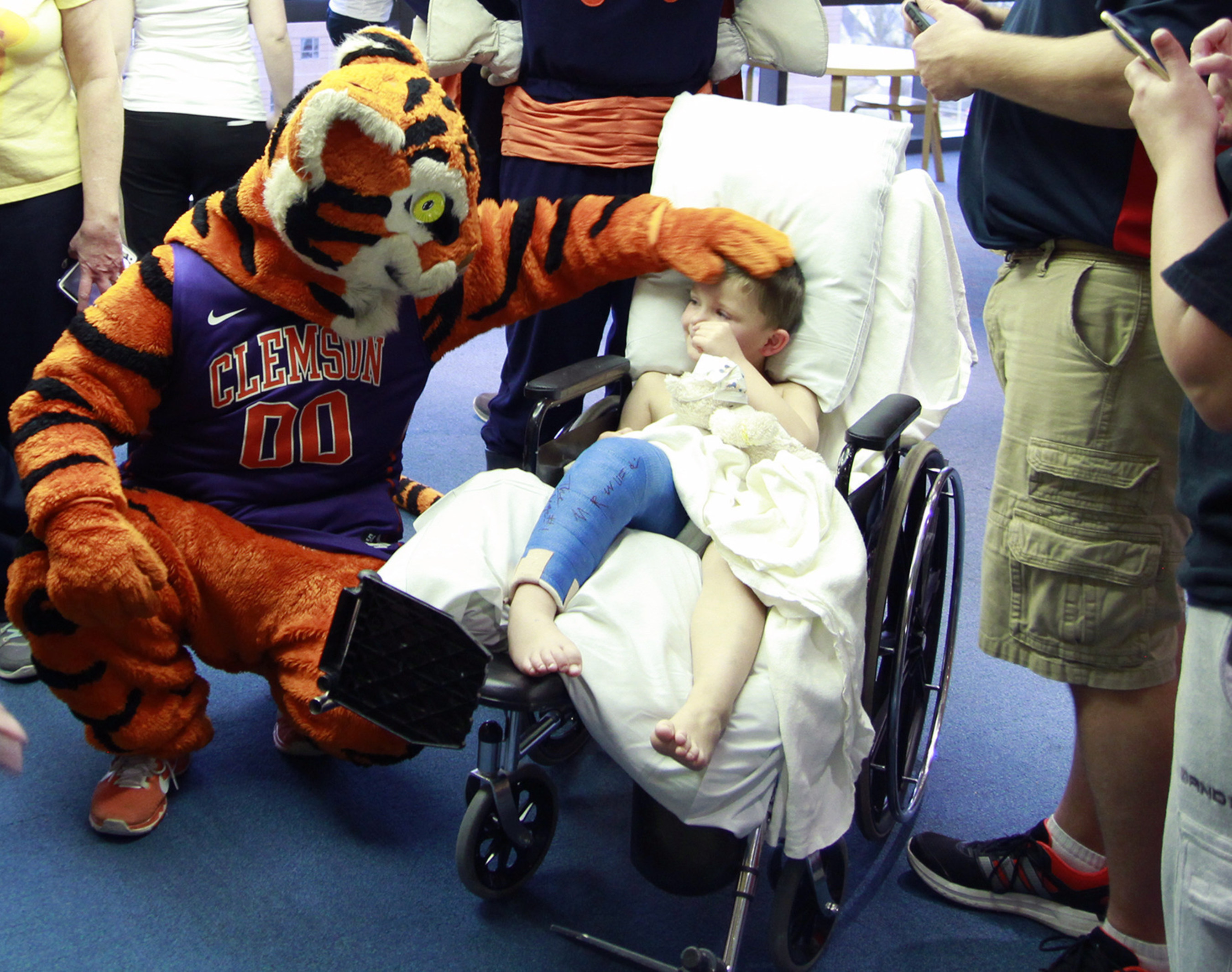 Four-year-old Kyler Rippey smiles as the Clemson Tiger wishes him well. The mascots of the Atlantic Coast Conference paid a visit to Brenner Children's Hospital as part of an outreach initiative for the 2015 ACC Men's Basketball Tournament.