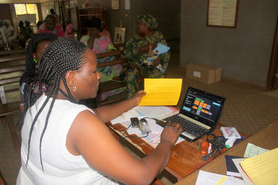 A health worker updates a vaccination record in the VaxTrac system.  (PRNewsFoto/VaxTrac)