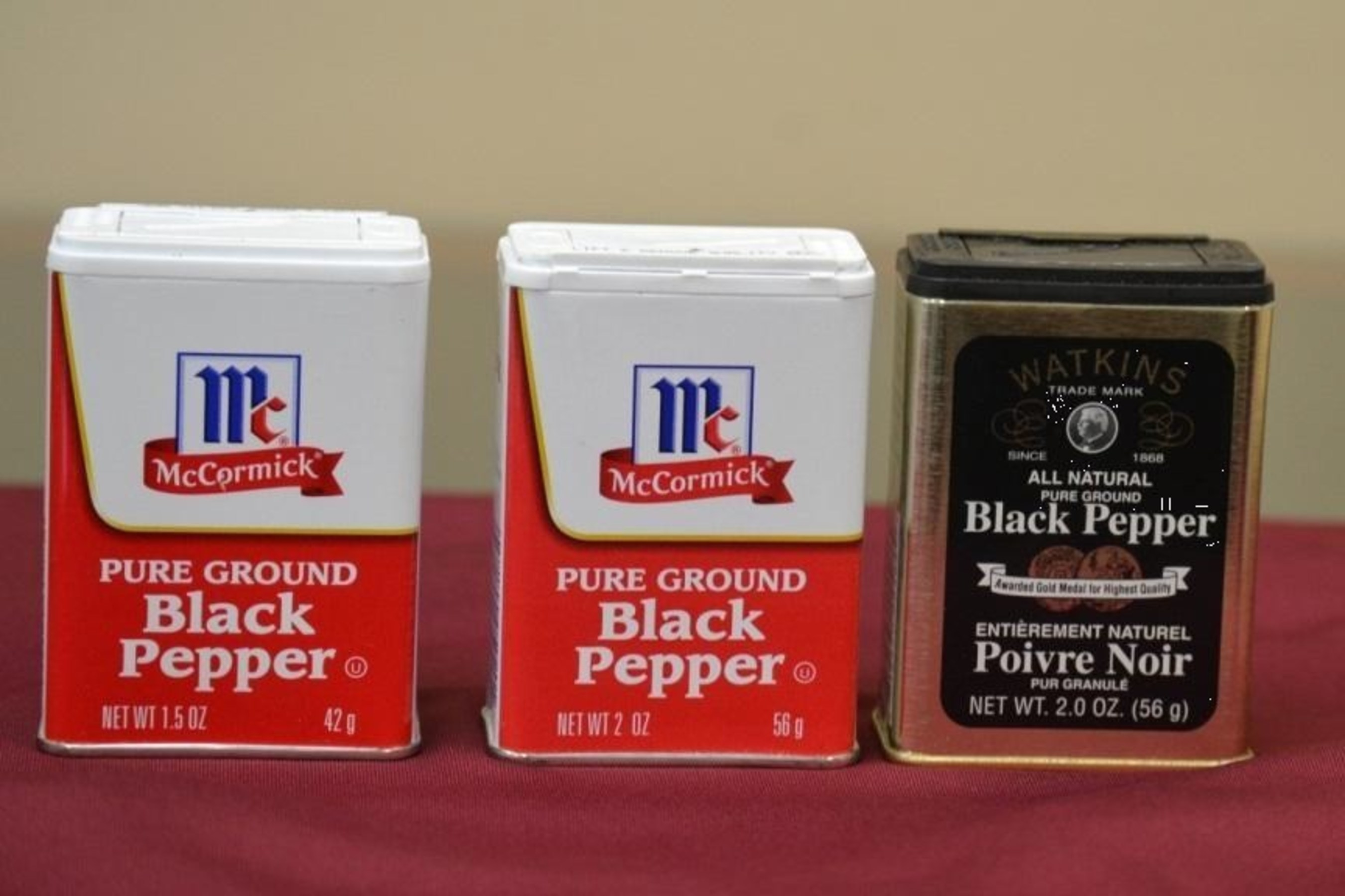 Photo showing traditional McCormick Small Tins with 1.5-ounce slack-fill and with traditional 2-ounce fill along with Watkins tin with 2-ounce fill.