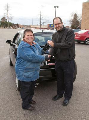 Bay City resident Sandy Gelisse receives the keys to her brand new Fiat. Gelisse won the car during Art Van Furniture's Black Friday festivities.  (PRNewsFoto/Art Van Furniture)