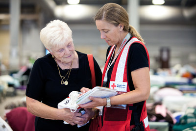 Doreen Ulm, 81, survived air raids in London during World War II, and now because of the flooding in Louisiana, she's at a shelter for the first time since the war. She shared her story with Red Cross relief worker Lynette Nyman, at the Red Cross shelter in Gonzales, Louisiana. Red Cross Photo by Marko Kokic