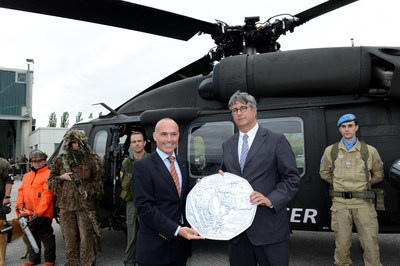 Gerald Klug (left) Austria's Minister of Defence and Sports, and Gerhard Starsich, CEO of the Austrian Mint, show off an enlarged copy of the new silver coin bearing an engraving of an S-70 BLACK HAWK helicopter. A ceremony to unveil the coin took place May 6 at the Brumowski Air Base in Langenlebarn near Vienna. The coin was issued to commemorate the 60th anniversary of the formation of the Austrian Armed Forces.  Austrian Mint photo.