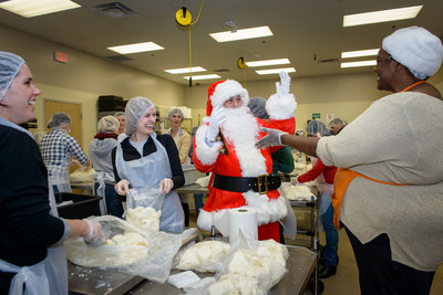 After handing over the keys to the new truck, Santa and his elves from Mercedes-Benz Financial Services spread holiday cheer among Forgotten Harvest employees and volunteers packaging meals to distribute to local families in need.