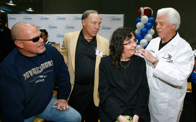Indianapolis mom Catherine Donaldson, age 52 and declared legally deaf, is surprised with a set of new, state-of-the-art hearing aids thanks to a letter from her daughter to Starkey Hearing Foundation. Providing assistance to Bill Austin, Founder, Starkey Hearing Foundation (right) was Joe DeLamielleure (center), NFL Hall of Famer, Buffalo Bills Offensive Guard (1973-1985), and retired Chicago Bears Quarterback Jim McMahon (far left). Photography Credit: Los Enterprises for Starkey Hearing Foundation.  (PRNewsFoto/Starkey Hearing Foundation)