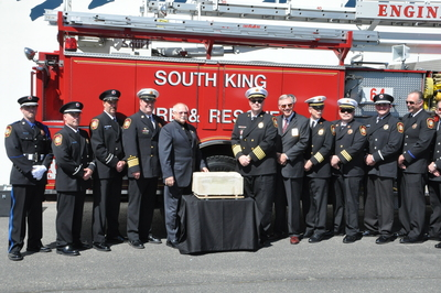 Members of the South King Fire and Rescue department pose with the 150 pound, Pentagon artifact outside Alaska Air Cargo in Seattle. The piece flew 2,700 miles to Seattle on Alaska Airlines Flight 1 and will soon be part of the district's 9/11 memorial.
