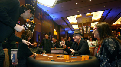 Starkey Hearing Foundation Founder, Bill Austin, looks on as Steve Martin (center) goes all in at the final table as Phil Hellmuth Jr. (left) gives the play by play.