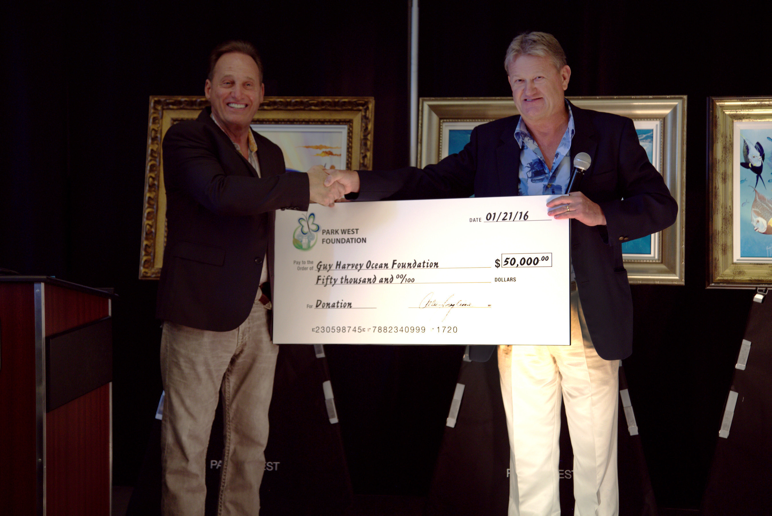 Park West Gallery Founder and CEO Albert Scaglione presents artist Guy Harvey with a $50,000 check to benefit his Guy Harvey Ocean Foundation. (Credit: Park West Gallery)