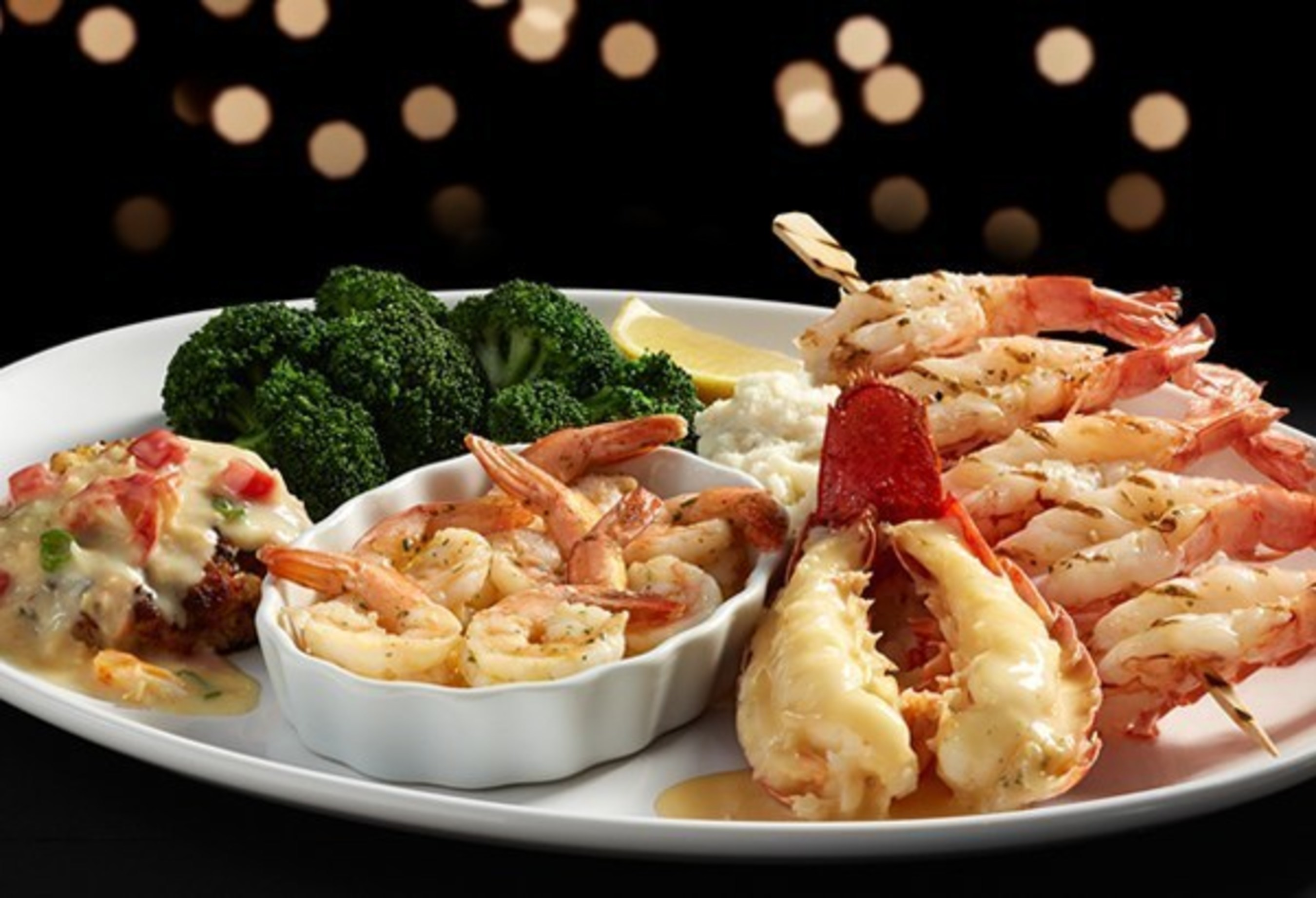 Red Lobster's NEW! Grand Seafood Feast features a wood-grilled Maine lobster tail with a white wine and butter sauce, a crab hollandaise-topped lump crab cake, a garlic-grilled red shrimp skewer and Red Lobster's signature hand-crafted garlic shrimp scampi.