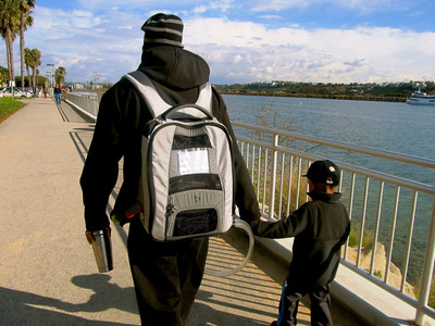 December 2012: SynCardia Total Artificial Heart patient Chad Washington enjoys a stroll with his 4-year-old son while wearing his Freedom portable driver in the Backpack, which powers his Total Artificial Heart. Mr. Washington was discharged from Ronald Reagan UCLA Medical Center on Dec. 10, 2012, and is currently waiting for a matching donor heart at home with his wife and son.  (PRNewsFoto/SynCardia Systems, Inc.)
