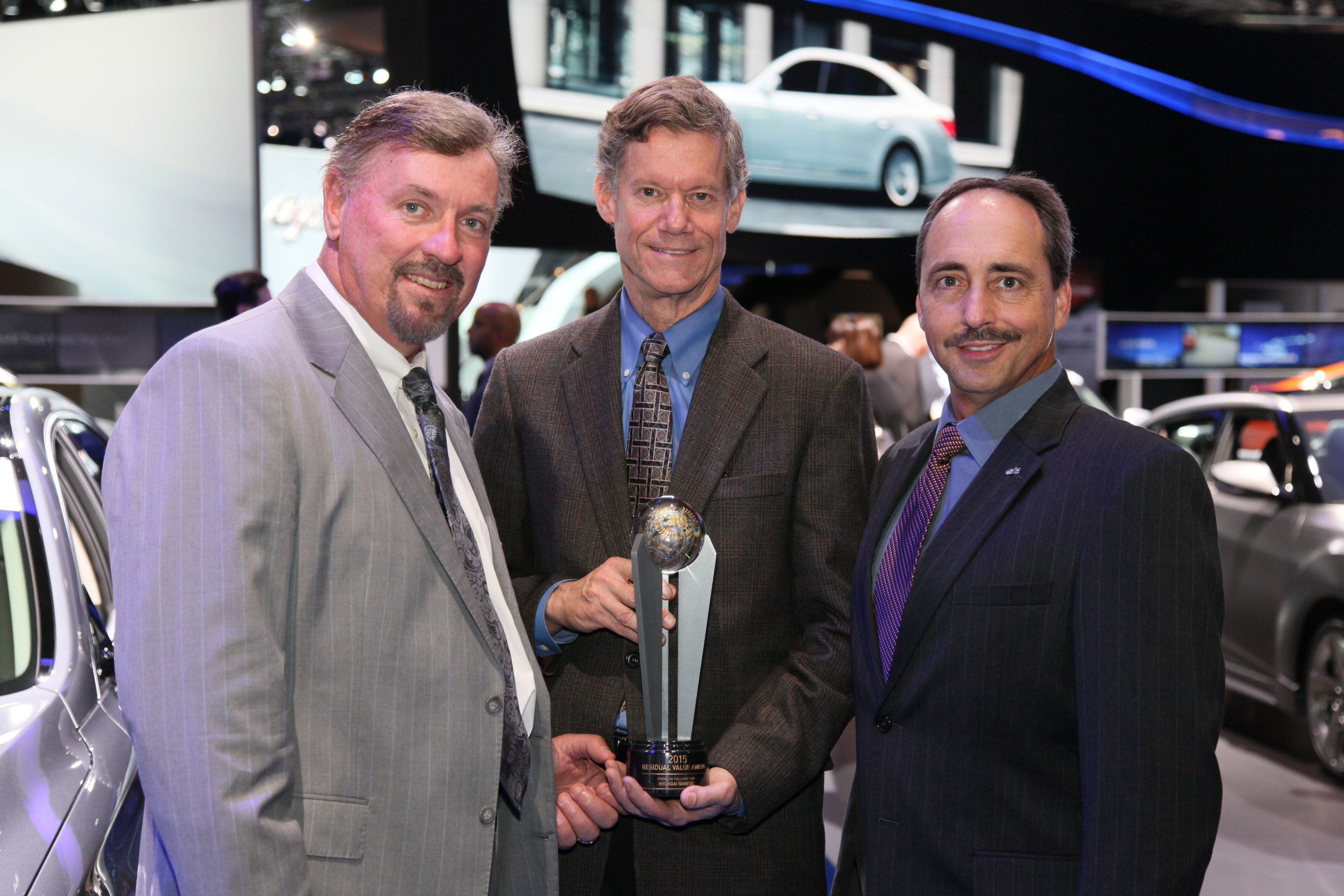 Larry Dominique, president, ALG hands the ALG Best Residual Value award for the Premium Full-Size Car Segment that 2015 Genesis won to Dave Zuchowski, president and CEO, Hyundai Motor America and Mike O'Brien, vice president, corporate and product planning, Hyundai Motor America (center).