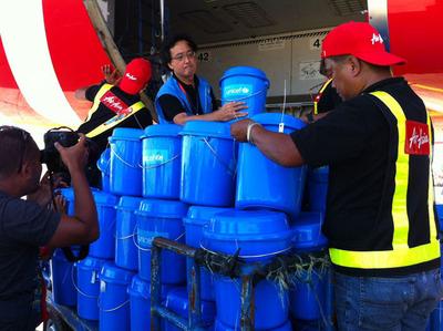 UNICEF Philippines Representative Tomoo Hozumi unloads hygiene kits today from an AirAsia flight arriving in Tacloban. (PRNewsFoto/U.S. Fund for UNICEF) (PRNewsFoto/U.S. FUND FOR UNICEF)