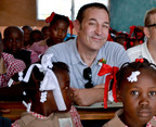 """""""Simpsons"""" co-creator and children's advocate Sam Simon visits with children at a Save the Children-supported school in Haiti in 2011. Contributed photo."""