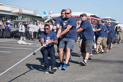 Russell Wilson and his team defeated actor and comedian Joel McHale during the Alaska Airlines Plane Pull benefiting Strong Against Cancer at the Museum of Flight in Seattle on Tuesday, July 28, 2015. Team Wilson pulled the 737 in 16.9 seconds, with Team Joel coming in at over a minute. (AP images)