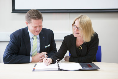 Matthew Hawkins, president of Sunquest Information Systems, signs the contract with Dr. Tracey Batten, chief executive officer of North West London Pathology Consortium.