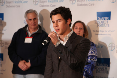 Nick Jonas, for Bayer Diabetes Care, addresses the crowd at Carnival for a Cure benefiting the Diabetes Research Institute, as the DRI Foundation's Robert A. Pearlman and Bayer HealthCare's Dr. Holly Schachner look on. (PRNewsFoto/Diabetes Research Institute Foundation, Sarah Merians Photography)