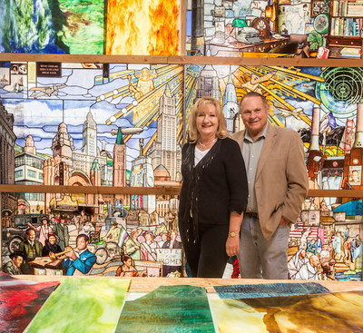 Utah philanthropists Debbie and Marc Bingham stand in front of the Roots of Knowledge stained glass art installation