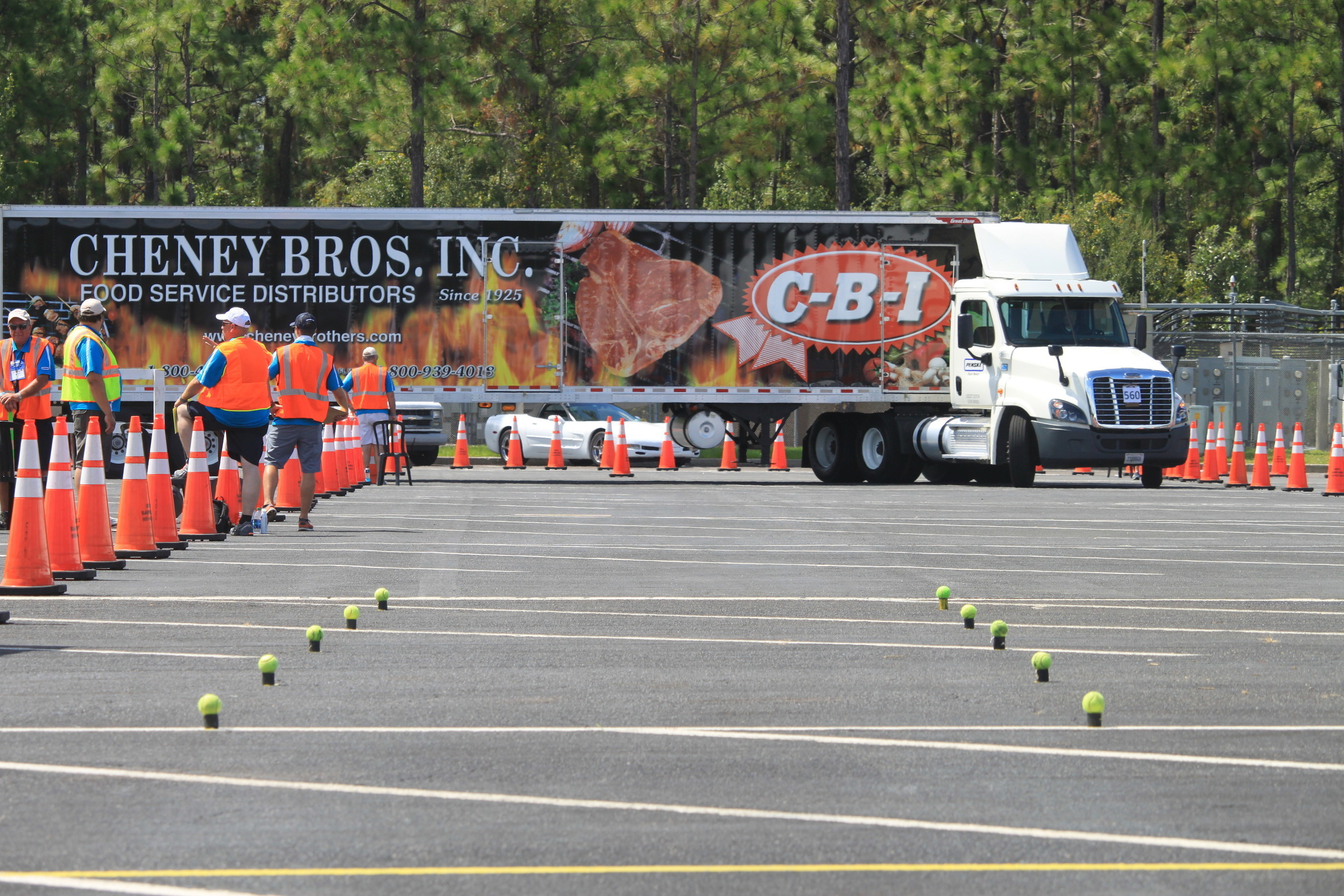 """In the U.S., foodservice distributors deliver about 25 million cases of food and other products each day to restaurants and other professional kitchens. During the IFDA Truck Driving Championship (above), a driver in the 48-foot tractor-trailer category takes on the """"right turn"""" challenge where a rear axle tire had to be within 18 inches of the cone to score."""