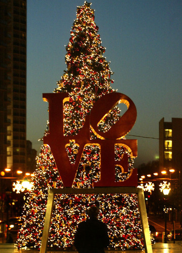 A passerby admires the Christmas tree on display behind Robert Indiana's famous Love statue in ...