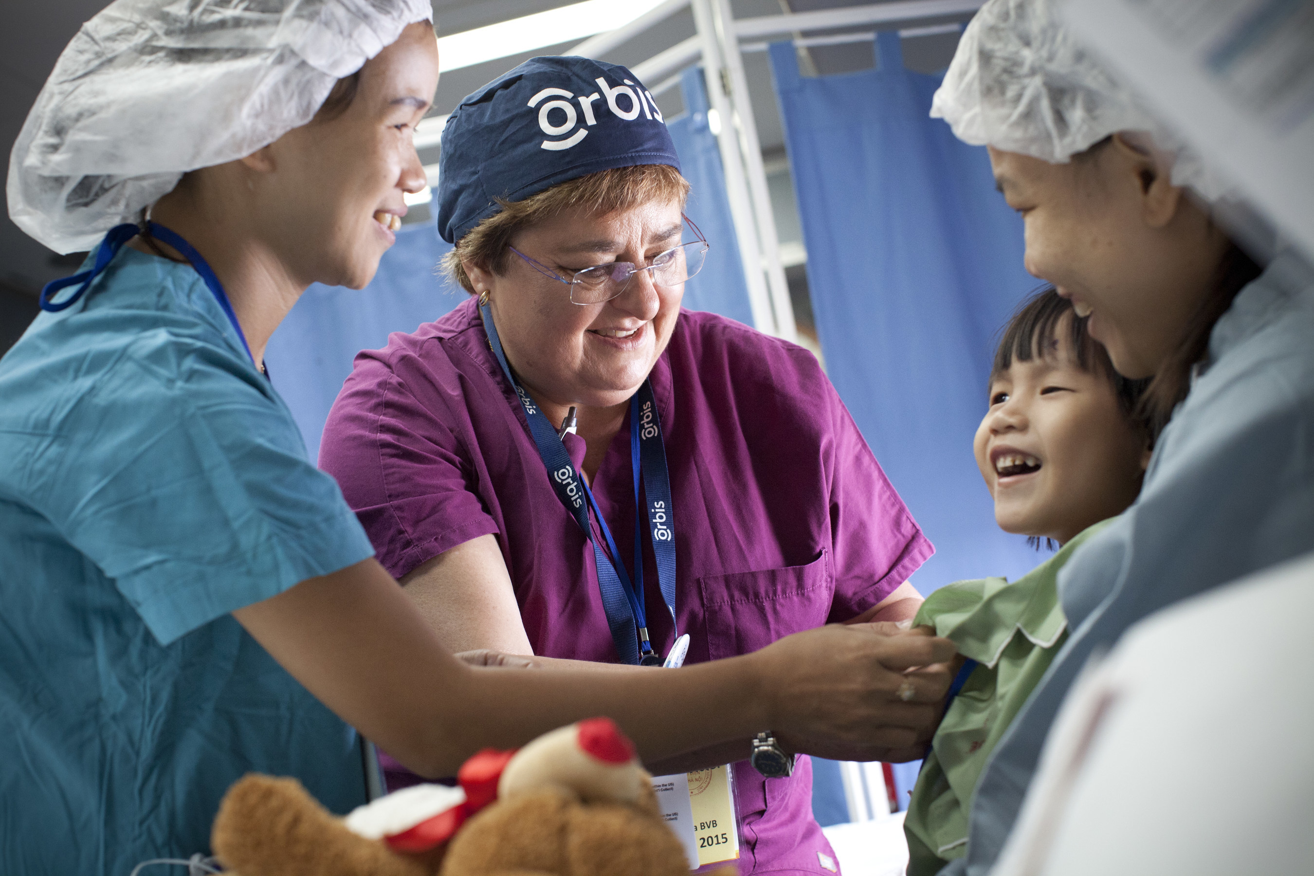 Orbis volunteer ophthalmic nurse, Cherelyn Victor, RN, works in the FEH recovery room to prepare Minh, 4, for treatment during the May 2015 FEH program held in Hue, Vietnam. Learn more: orbis.org (photo: Geoff Bugbee/Orbis).