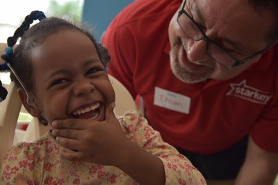A young girl in the Dominican Republic celebrates hearing for the first time with Bayat Foundation Chairman Ehsan Bayat