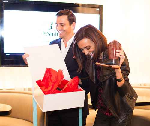 Special guests Bill and Giuliana Rancic open a gift of Texas cowboy boots for son Duke given by representatives of Dr. Smith's Diaper Rash for the brand at a national launch party held at RPM Italian in Chicago. (PRNewsFoto/Mission Pharmacal Company) (PRNewsFoto/MISSION PHARMACAL COMPANY)