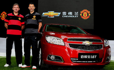 "Legendary former Manchester United captain Bryan Robson, (left), affectionately known to fans during his career as ""Captain Marvel"" with Ryan Giggs in Shanghai, China with a Chevrolet Malibu.  Global auto maker, Chevrolet is entering into a five-year partnership agreement with Barclays Premier League giant Manchester United to become the club's Official Automotive Partner.  (PRNewsFoto/General Motors)"