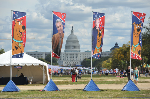 Flags of Cesar Millan and Scooby-Doo frame the U.S. Capitol during the Second Annual National Family Pack Walk on Saturday Sept. 29, 2012, in Washington. (PRNewsFoto/Larry French/Invision for Warner Bros. Consumer Products/AP Images).