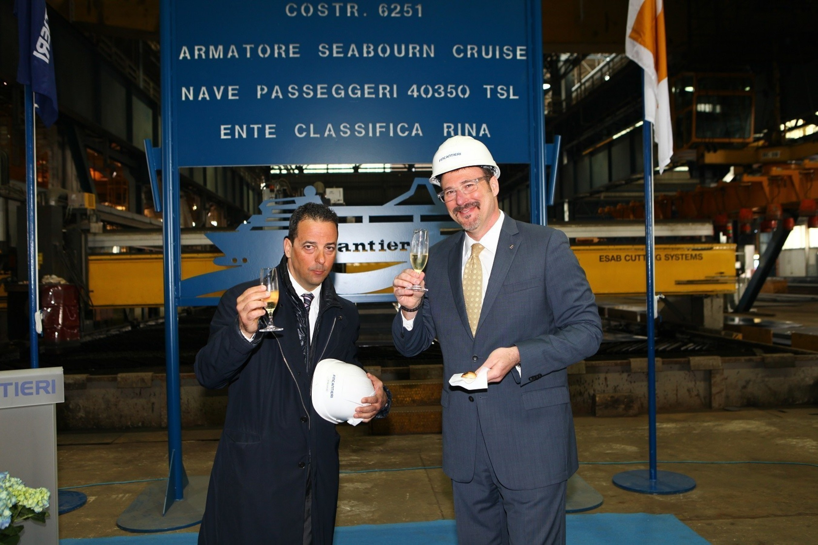 Antonio Quintano, Director of Fincantieri's Marghera shipyard, and Richard Meadows, Seabourn President, toast to the first steel cut for the line's newest ship, Seabourn Encore.