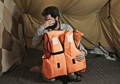 """32 year old Ismail Nerabani from Hums, Syria reacting to the life jacket bearing his life story, as he sees it for the first time. The French teacher is temporarily staying in the refugee camp """"Oreokastro"""" in Thessaloniki, Greece. In October 2016, as part of """"Project Life Jacket"""", the life stories of nine Syrian refugees were illustrated on life jackets used for the crossing to Lesbos.Picture taken on the 7th October 2016 in Thessaloniki. (Project Life Jacket). (PRNewsFoto/Project Life Jacket)"""
