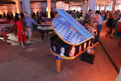 """Guests enjoy and play 88 pianos at the Sing for Hope Pianos launch party on May 16. Each piano, designed by volunteer artists, will live on the streets of New York City from June 1-16 as part of Sing for Hope's mission of """"Art for All.""""  (PRNewsFoto/Sing for Hope)"""
