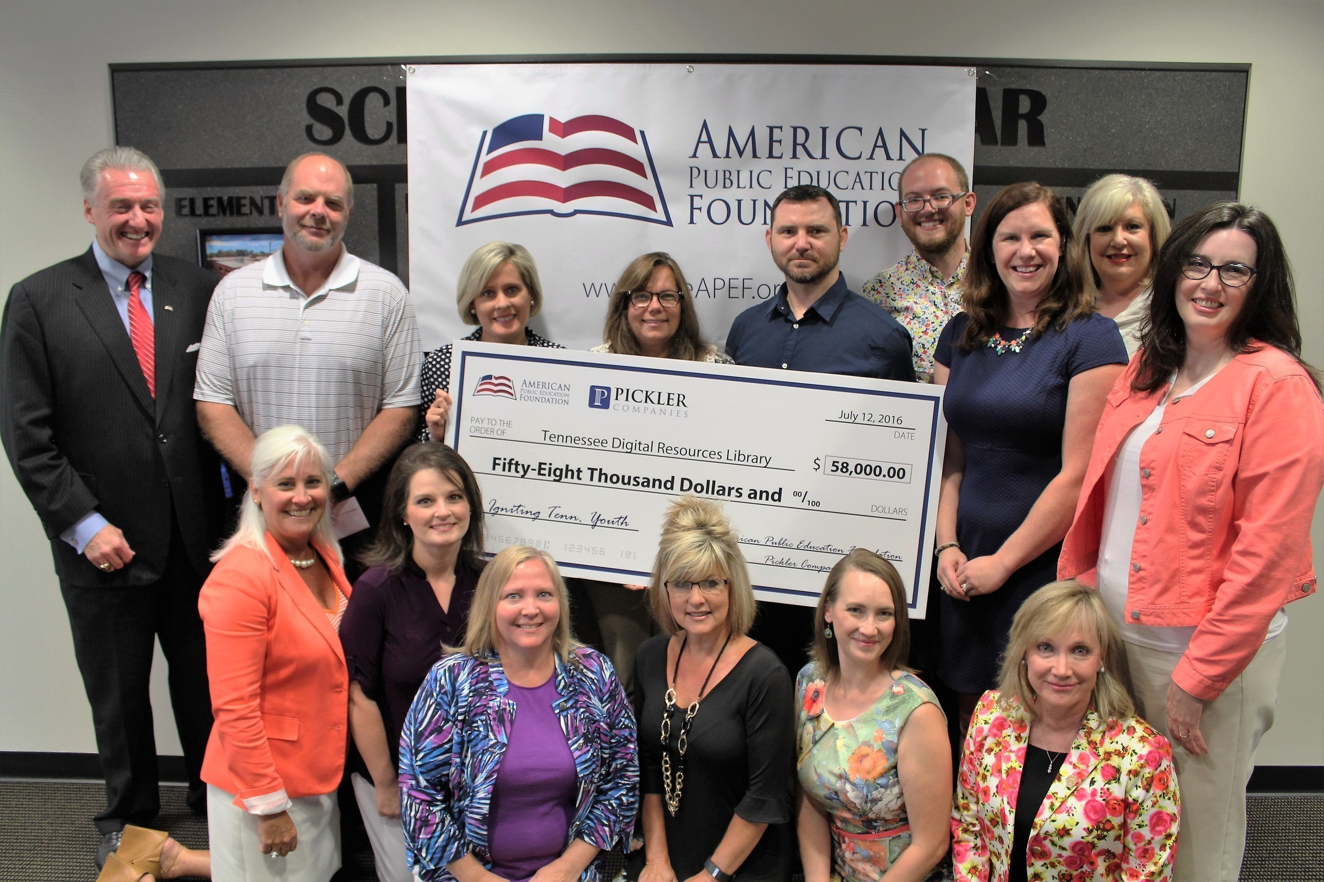 David Pickler, J.D., President, American Public Education Foundation (top left), presents a $58,000 check and iPad Air 2s to the 58 Tennessee high school teachers (partial group shown) who curated digital content for the Tennessee Digital Resources Library. Also shown (lower left) is Tammy Grissom, Ed.D., Executive Director, Tennessee School Boards Association.
