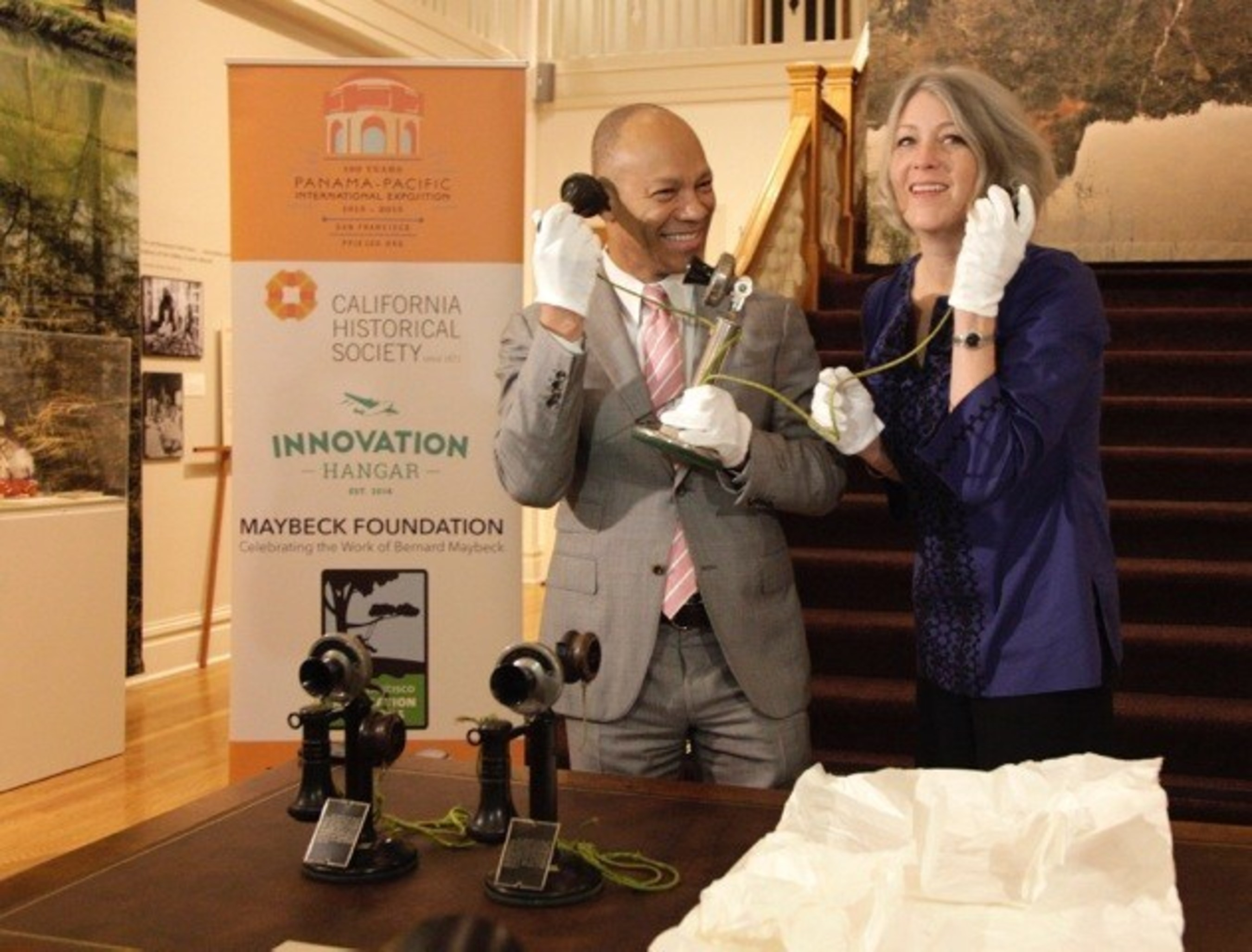 "Ken McNeely, President of AT&T California and Dr. Anthea Hartig, Executive Director of the California Historical Society, unpack the original phone used by President Woodrow Wilson to make the first-ever transcontinental phone call on January 25, 1915. The four original phones used for the call were unveiled today and will be on display at the California Historical Society as part of its PPIE100 ""City Rising: San Francisco and the 1915 World Fair"" exhibition at 678 Mission Street which officially opens on February 22nd in San Francisco. City Rising, will also feature a sister exhibition at the Palace of Fine Arts which opens February 21st as part of a city-wide celebration and community day at the Palace that marks the 100th anniversary of the 1915 World's Fair. Photo Source: Michael Tweed"