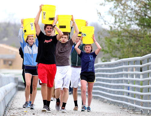 FFA members and fellow students from Hamilton Southeastern High School in Fishers, Ind., carry five-gallon ...