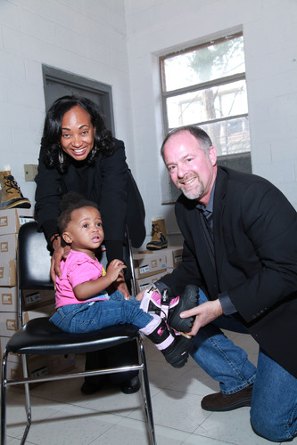 "Michael Rouse, vice president of Philanthropy and Community Affairs at Toyota Motor Sales, USA, and colleague Alva Mason, diversity manager at Toyota, help a young girl find a pair of new boots at Toyota's ""Walk In My Boots"" community outreach project in Detroit, earlier today.  In its second year of event sponsorship, Toyota provided 200 pairs of new boots to several homeless families being supported by the Salvation Army's Denby Center.   The automaker also made a $10,000 donation to the Salvation Army of Metro Detroit.  ..."