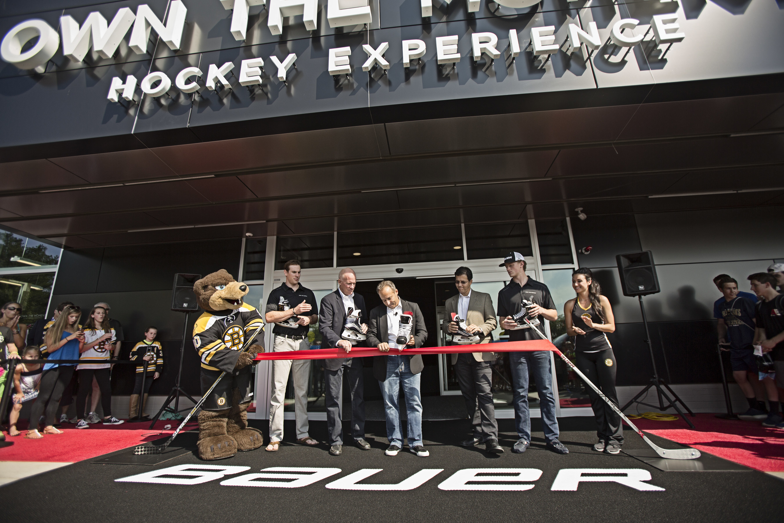 Buffalo Sabre Jack Eichel, and Boston Bruin Jimmy Hayes look on as Performance Sports Group CEO Kevin Davis cuts the ribbon at the grand opening of the Bauer Hockey OWN THE MOMENT Hockey Experience